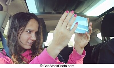 Smiling young woman taking selfie picture with smart phone camera in car in slow motion.