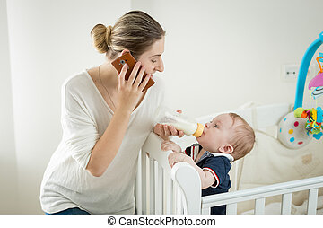 Smiling young woman talking by phone while feeding her baby son