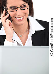 Smiling young woman talking on a cellphone while using a laptop computer
