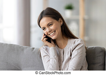 Smiling young woman talking on phone, sitting on sofa at home