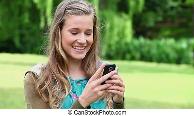 Smiling young woman typing on her cellphone