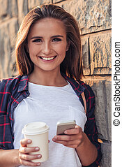 Smiling young woman using a cellphone in the city