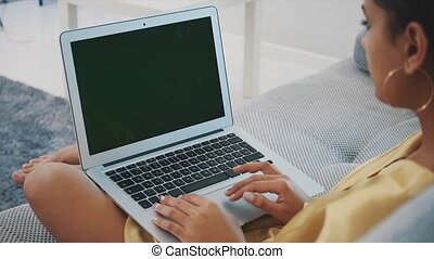 Smiling young woman using a laptop at home as she relaxes on a comfortable sofa. An attractive fun model with a computer typing. Green screen.