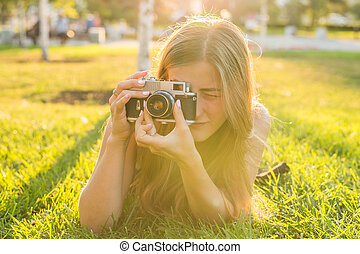 Smiling young woman using a retro camera to take photo at the park.