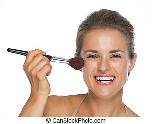 Smiling young woman using brush