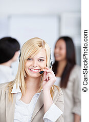 smiling young woman using headset in the office