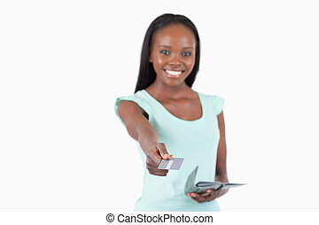 Smiling young woman using her credit card to pay against a...