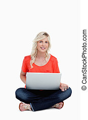 Smiling young woman using her laptop while sitting...