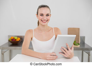 Smiling young woman using her tablet pc looking at camera