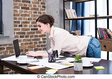 Smiling young woman using laptop at desk with papers and office supplies