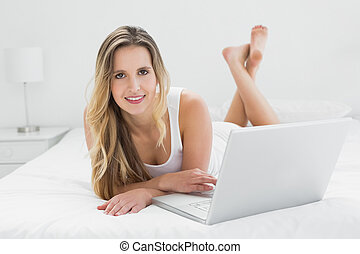 Smiling young woman using laptop on bed
