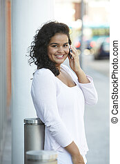 Smiling Young Woman Using Mobile Phone In Urban Setting