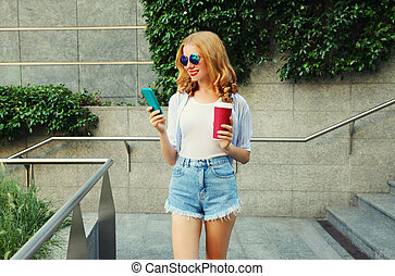 smiling young woman using smartphone with coffee cup in the city