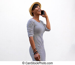 Smiling young woman walking and talking on cell phone