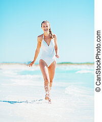 Smiling young woman walking at seaside