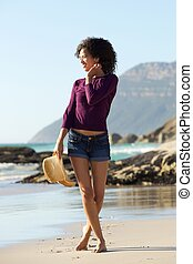 Smiling young woman walking on beach