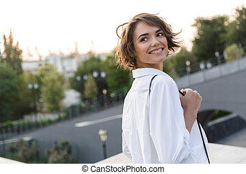 Smiling young woman walking outdoors