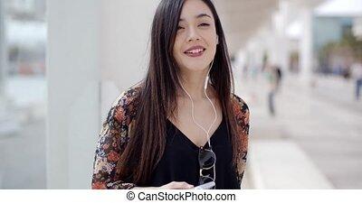 Smiling young woman walking through town