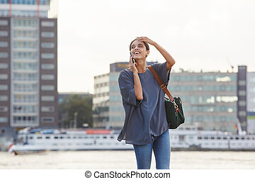 smiling young woman walking with a bag and talking on cell phone