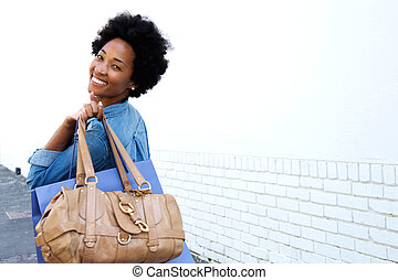 Smiling young woman walking with bags