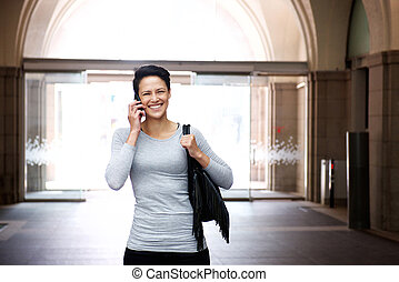 Smiling young woman walking with cellphone and bag