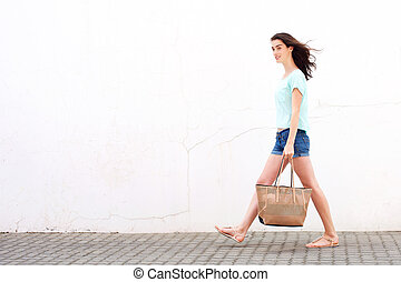 Smiling young woman walking with handbag