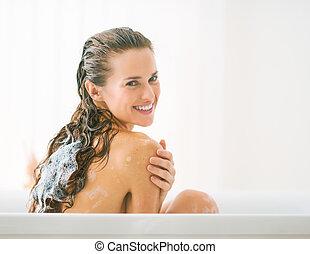 Smiling young woman washing hair in bathtub