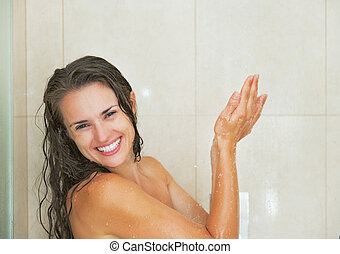 Smiling young woman washing in shower
