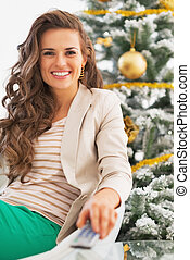 Smiling young woman watching tv in front of christmas tree