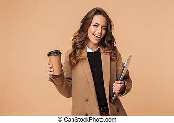 Smiling young woman wearing a coat standing