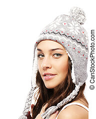 smiling young woman wearing winter cap on white background