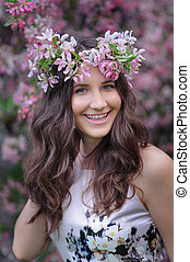 smiling young woman with a wreath on her head on a background of flowering spring trees