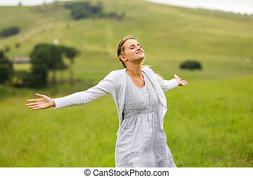young woman with arms open on grassland - smiling young ...