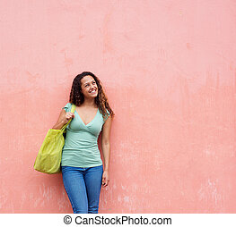 Smiling young woman with bag standing against wall