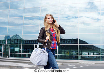 Smiling young woman with bag walking and talking on cellphone