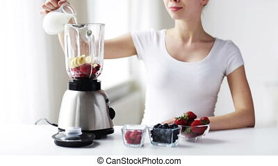 smiling young woman with blender making milk shake - healthy...