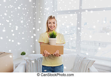 smiling young woman with box and plant at home