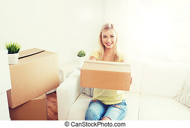 smiling young woman with cardboard box at home