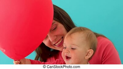Smiling young woman with child holding balloon - Happy young...