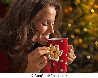 Smiling young woman with christmas cookie and cup of hot chocolate