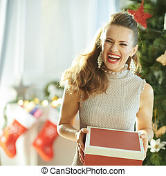 smiling young woman with Christmas gift near Christmas tree