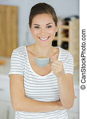smiling young woman with coffee cup at home