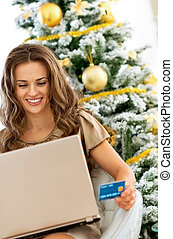 smiling young woman with credit card using laptop near christmas tree