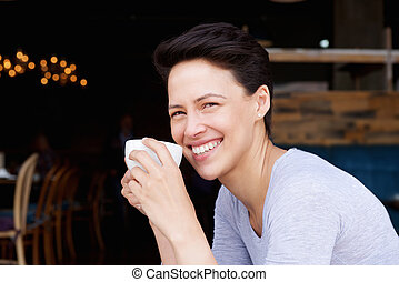 Smiling young woman with cup of coffee