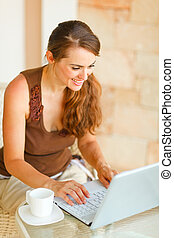 Smiling young woman with cup of coffee working on laptop on terrace