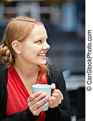 Smiling young woman with cup of chocomilk