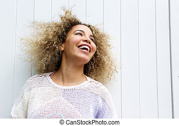 Smiling young woman with hair blowing in wind