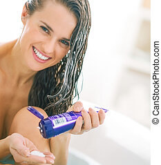 Smiling young woman with hair conditioner in bathtub