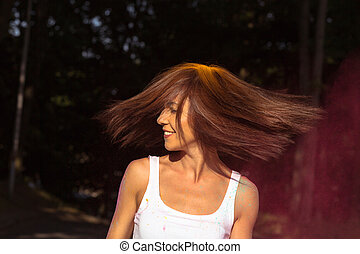 Smiling young woman with hair in motion celebrating Holi Festival