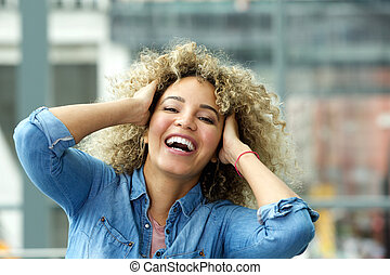 Smiling young woman with hands in hair
